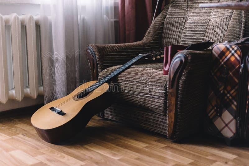 Ein Stapel alte Vinylaufzeichnungen und akustische hölzerne Gitarre mit einem Verstärker werden auf einem braunen Hintergrund für lizenzfreies stockbild