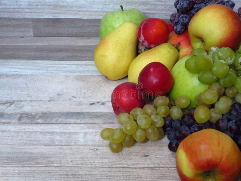 Ein Stapel der frischen organischen Herbstfrucht auf gebleichtem Eichenholzhintergrund Gesunde Diät/Frucht/Nahrung Obstgartenernt stockfoto