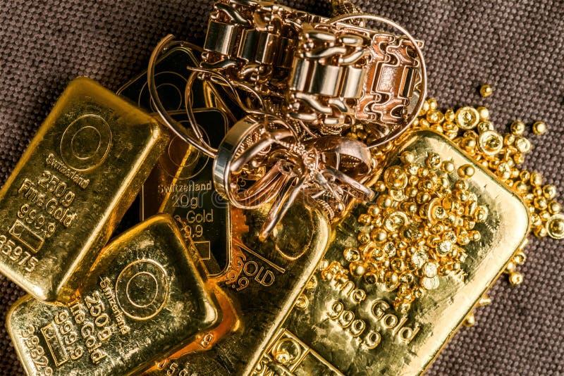 Ein Stapel des Goldbarrengoldschmucks und der Goldkörnchen auf dem Hintergrund zur groben Beschaffenheit des Gewebes stockbild