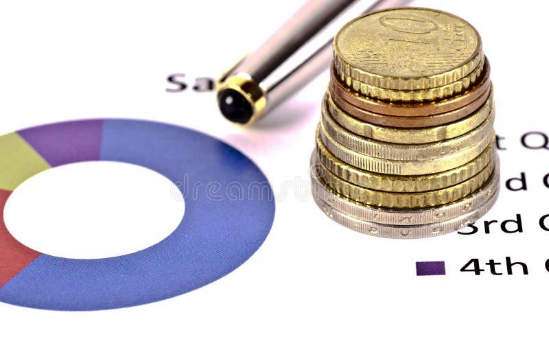 Ein Stapel Münzen über einem grafischen Finanzbericht stockbilder