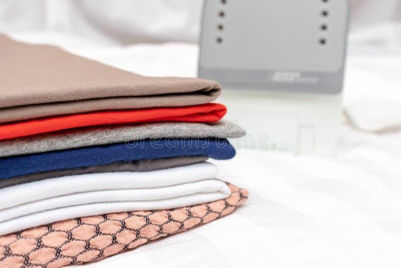 Ein Stapel mehrfarbige Kleidung nah oben mit dem weißen modernen elektrischen Eisen des Hintergrundes - Bügeln, Wäscherei und Hau stockfotografie