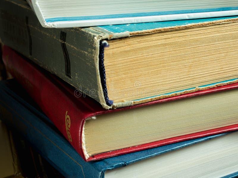 Ein Stapel neue und alte Bücher mit ausgefransten Abdeckungen und gelb gefärbten Seiten stockfotografie