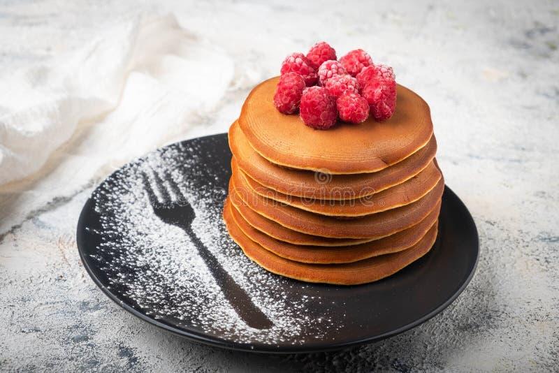 Ein Stapel Pfannkuchen auf einer Platte mit Himbeeren und Beerensoße stockbild