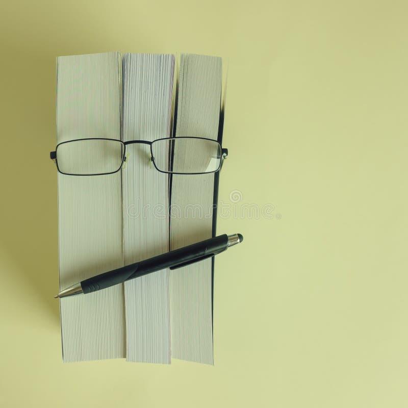 Ein Stapel starke neue Bücher, Gläser und ein Bleistift stellen ein Person ` s Gesicht dar Konzeptlesung, Vorbereitung für Prüfun stockfotos