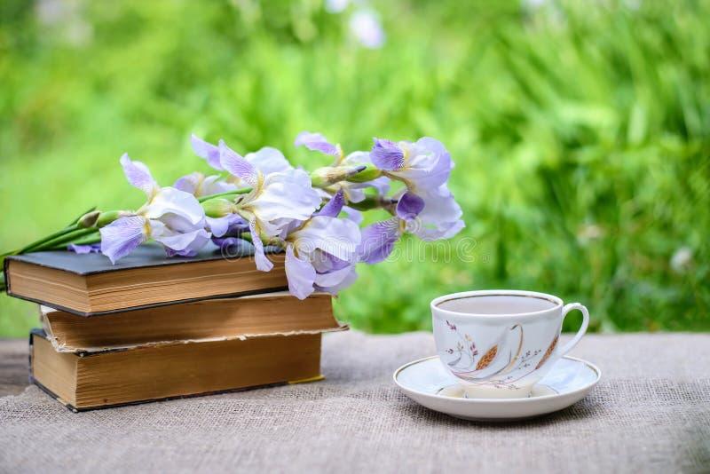 Ein Stapel von alten Büchern, von purpurroter Iris und von Tasse Tee lizenzfreie stockfotografie