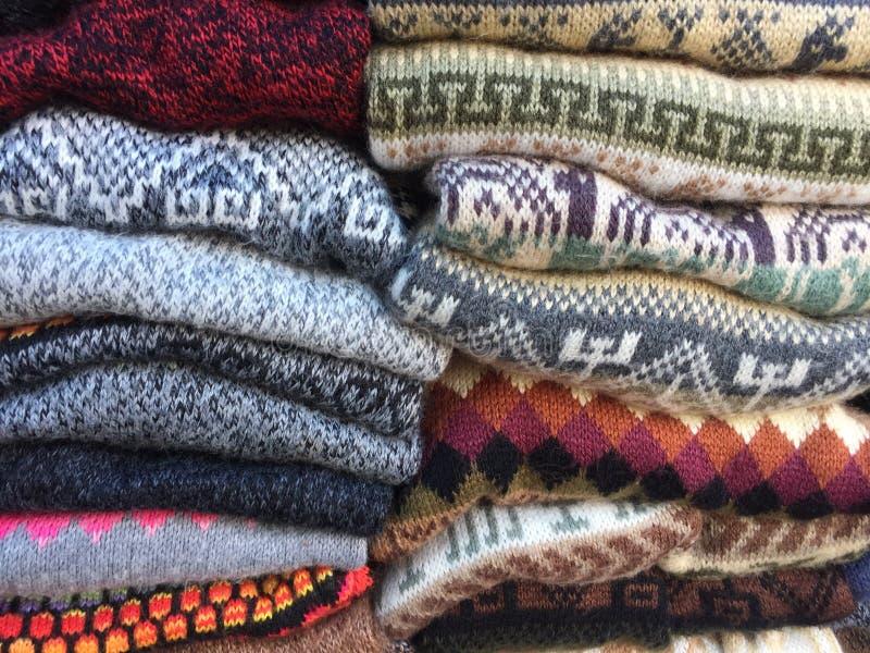 Ein Stapel von starken woolen Pullovern in einigen Farben machte eigenhändig in typischem Anden am berühmten Markt von Otavalo, E lizenzfreies stockbild