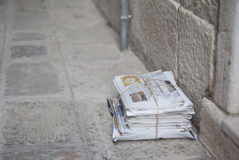 Ein Stapel von Zeitungen, gebunden mit Schnur SAT auf der Pflasterung in einer Straße in Venedig, Italien lizenzfreie stockfotos