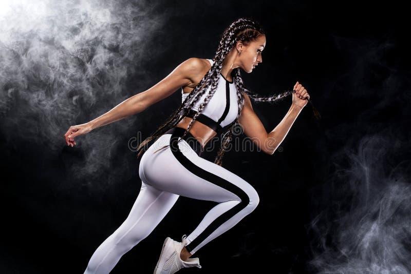 Ein starker athletischer, Frauensprinter, laufend auf dem schwarzen Hintergrund, der in der Sportkleidungs-, Eignungs- und Sportm stockfotos