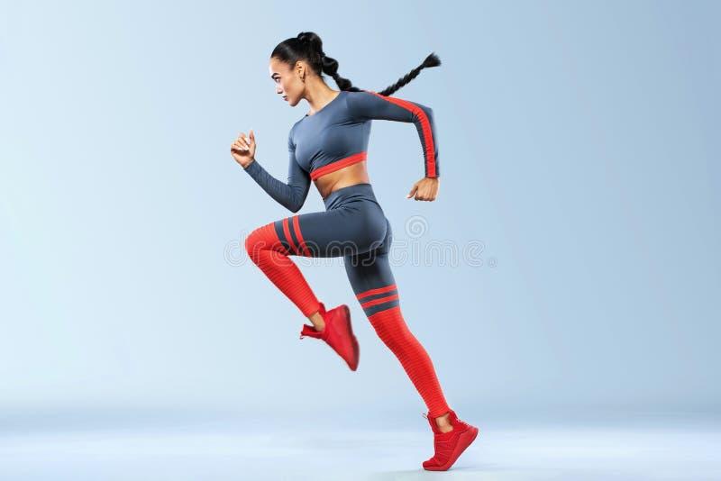 Ein starker athletischer, Frauensprinter, laufendes Tragen in der Sportkleidungs-, Eignungs- und Sportmotivation Läuferkonzept mi stockfoto