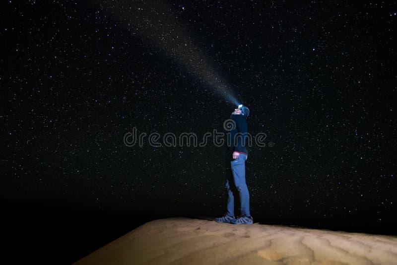 Ein stehender Mann, der den sternenklaren Himmel mit einer Taschenlampe, auf einer Düne in der Wüste des Ergs Chebbi betrachtet lizenzfreies stockbild
