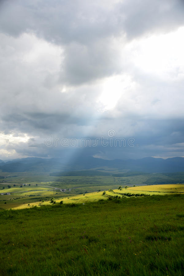 Ein steigender Sonnenstrahl die Erde an einem regnerischen Tag stockfoto