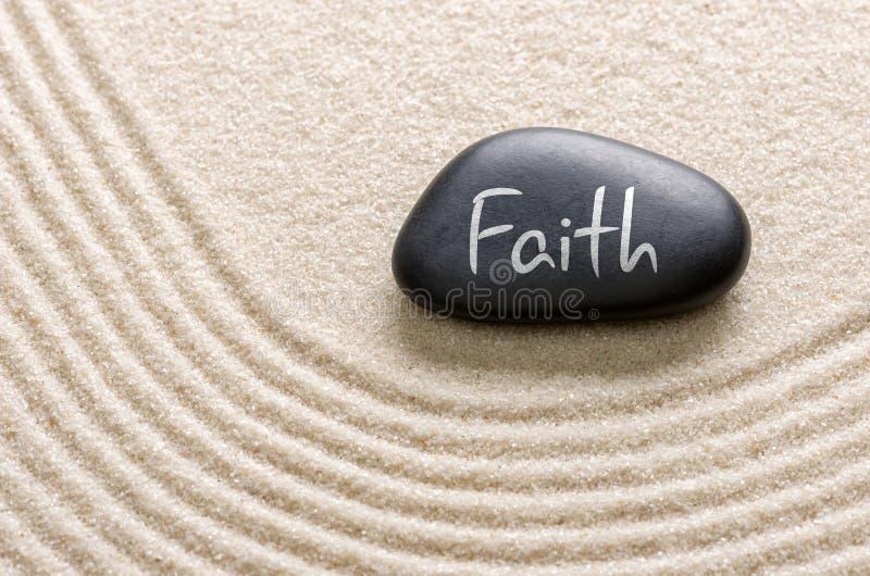 Ein Stein mit dem Aufschrift Glauben stockfotos