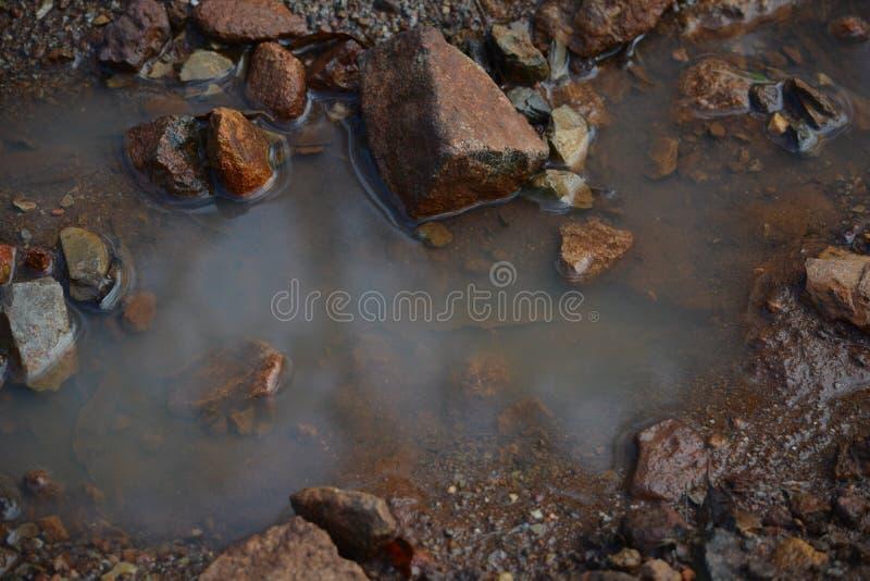 Ein Stilllebenbild einer Pfütze mit Felsen, die Frieden und Reflexion zeigt lizenzfreie stockbilder