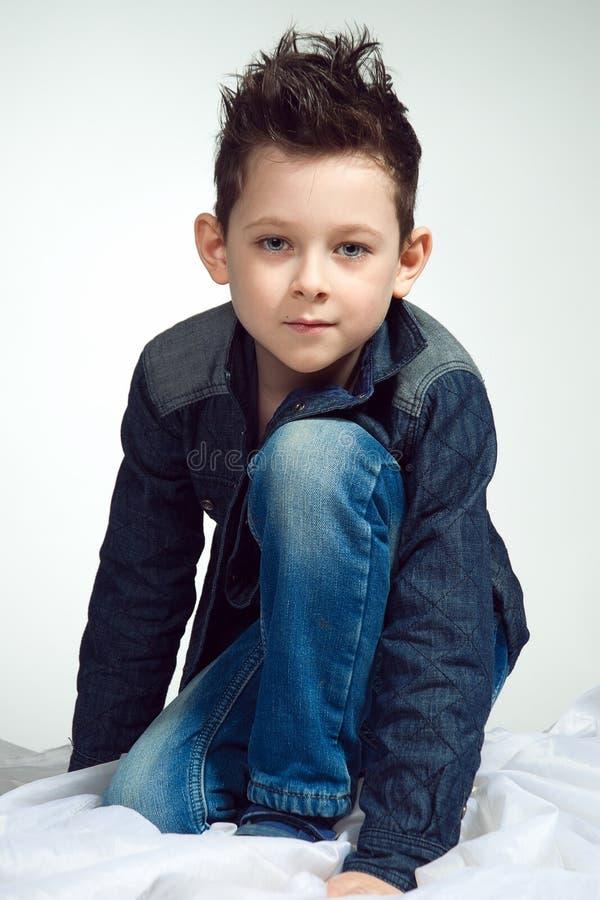 Ein stilvoller kleiner Junge ist so attraktiv Ein Kind sitzt auf seinem k lizenzfreies stockbild
