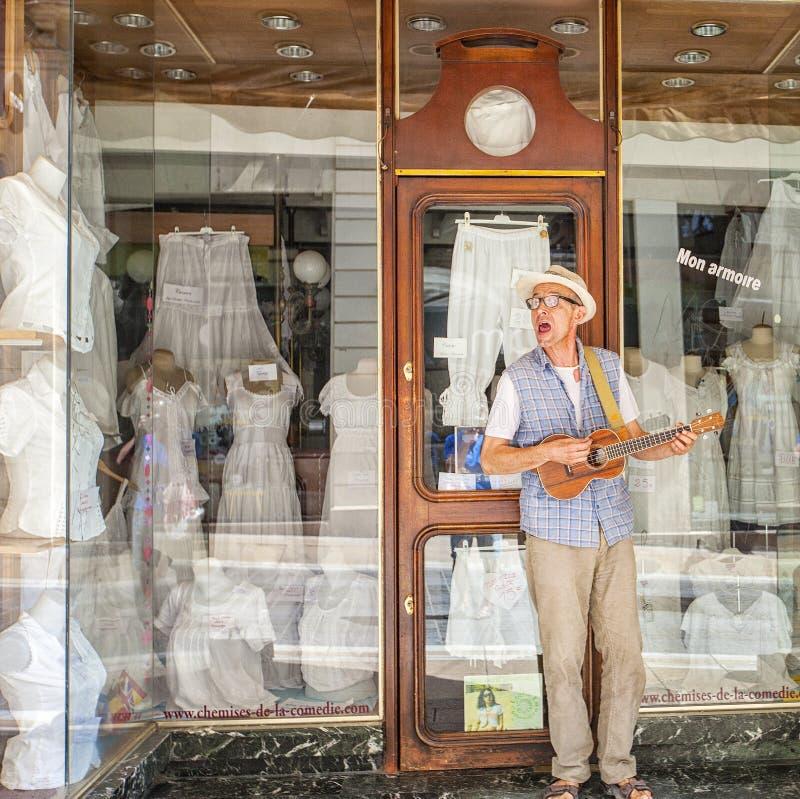 Ein Straßenmusiker, der im Kostüm in der Stadt von Montpellier, Frankreich spielt und singt stockfotografie