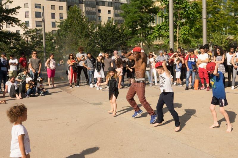 Ein Straßentänzer, der ein Tanzzeigung in einer Paris-Straße, unter Verwendung der Kinder in der Öffentlichkeit tut stockbild