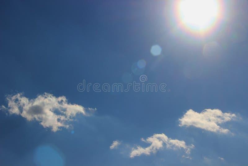 Ein Strahl der goldenen Sonne gegen einen hellen blauen Himmel mit kleinen Wolken stockfotos