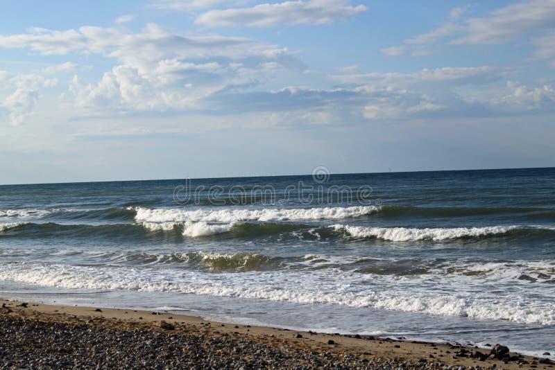 Ein Strand mit den Wellen, die an einem bewölkten Tag hereinkommen stockbilder