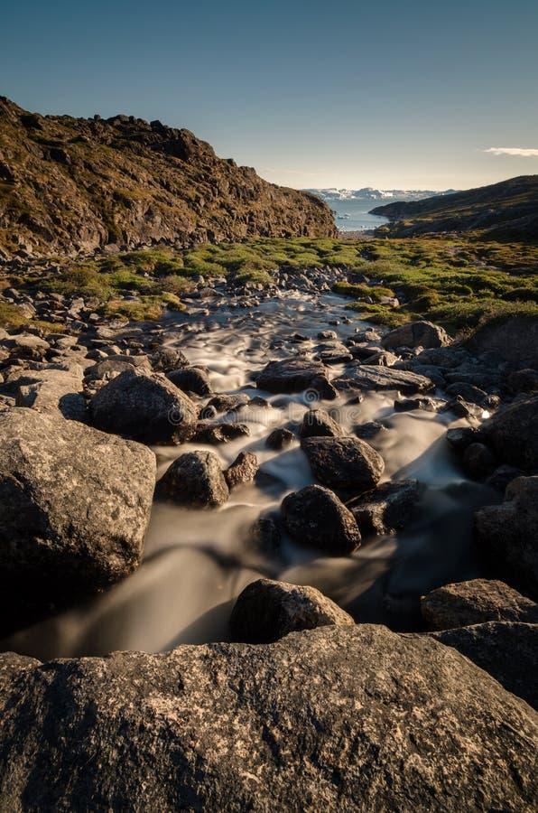 Ein Strom, der von einem Eissee in Richtung zum Ilulissat Icefjord, Grönland fließt stockfotos