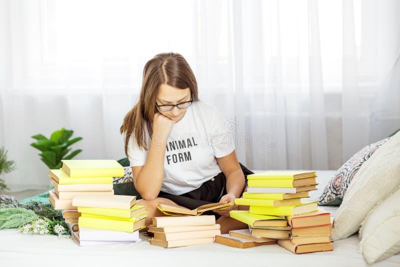 Ein Student bereitet sich für Prüfungen mit Gläsern vor Viele Bücher r stockfotografie