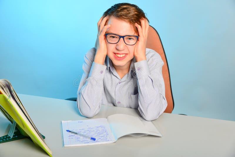 Ein Student mit Gläsern tut Hausarbeit, Schulhausarbeit an einem Schreibtisch mit Lehrbüchern Der Student bereitet sich für Prüfu lizenzfreie stockbilder
