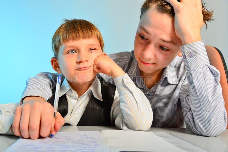 Ein Student mit Gläsern tut Hausarbeit, Schulhausarbeit an einem Schreibtisch mit Lehrbüchern Der Student bereitet sich für Prüfu stockbild