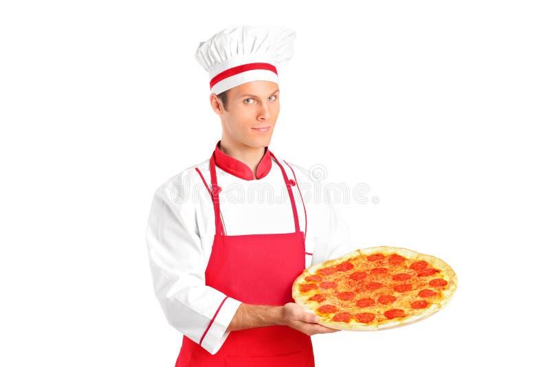 Ein Studio schoss von einem jungen Chef, der eine Pizza anhält lizenzfreies stockbild
