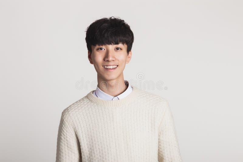 Ein Studioporträt eines asiatischen jungen Mannes, welche nach einer Kamera mit überzeugtem Lächeln sucht lizenzfreies stockbild