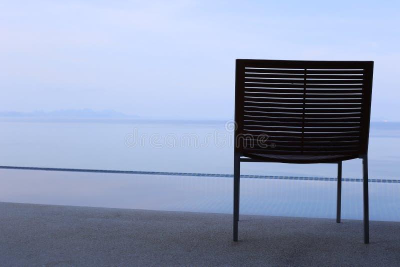 Ein Stuhl auf dem Balkon, der zum Meer gegenüberstellt lizenzfreie stockbilder