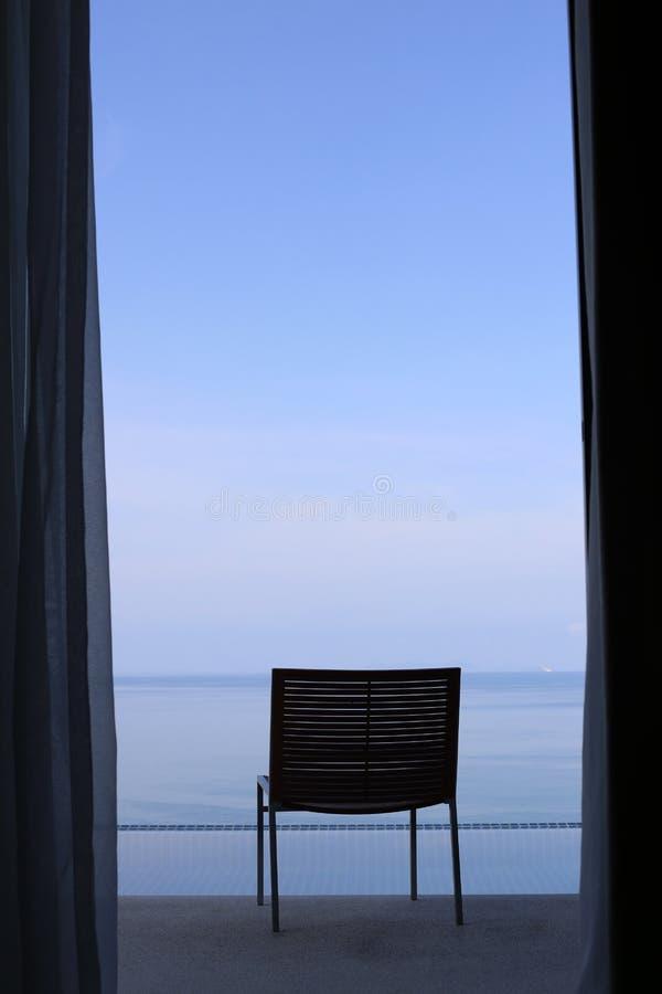 Ein Stuhl auf dem Balkon, der zum Meer gegenüberstellt lizenzfreie stockfotografie