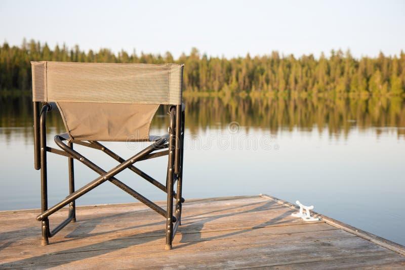 Ein Stuhl auf einem hölzernen Dock, das heraus auf einem See im Sommer schaut lizenzfreie stockfotos