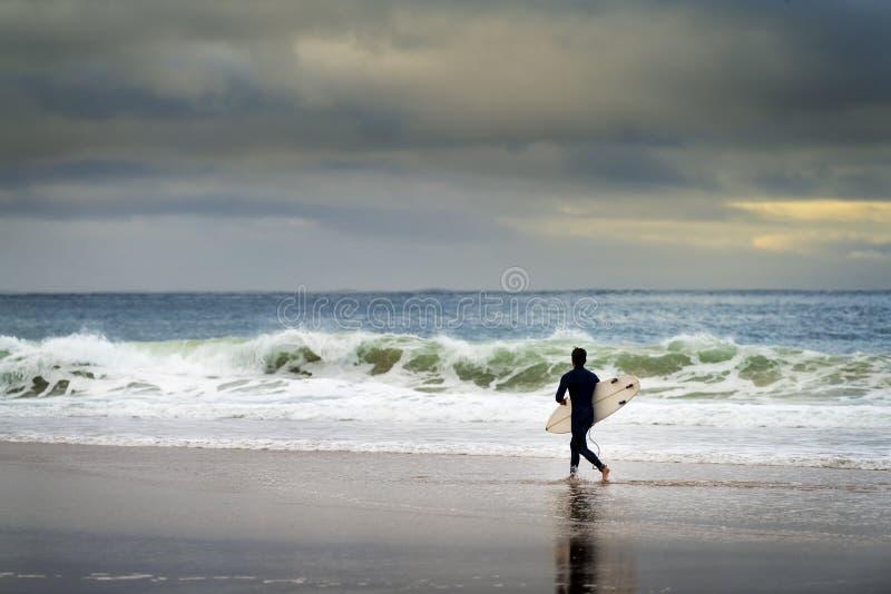 Ein Surfer betritt das Meer am Carcavelos Beach in Oeiras lizenzfreie stockfotografie