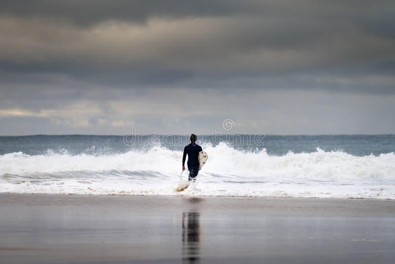 Ein Surfer betritt das Meer am Carcavelos Beach in Oeiras lizenzfreie stockfotos