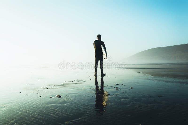 Ein Surfer, der ein Surfbrett silhouettiert gegen die Nachmittagssonne, an einem nebelhaften Wintertag hält Saunton, Devon, Großb lizenzfreies stockbild