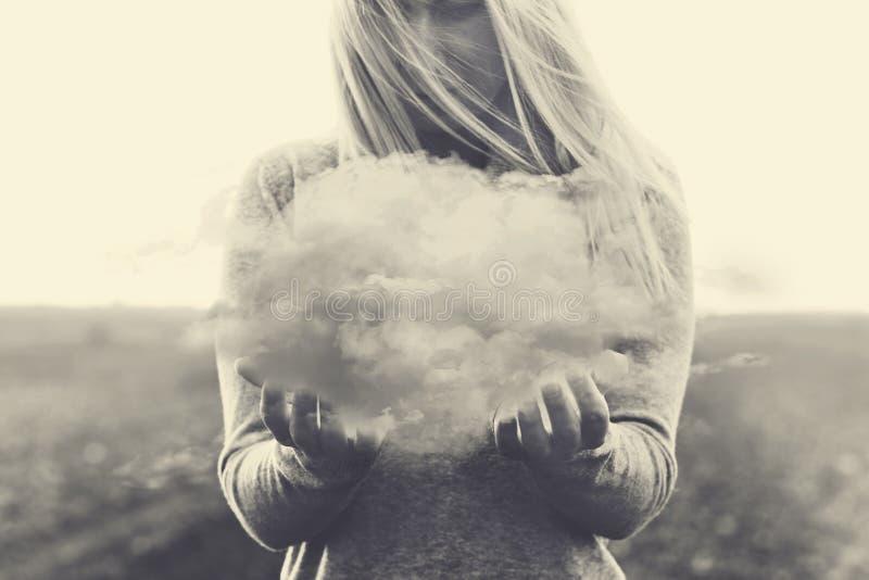 Ein surrealer Moment, alleine Frau, die in ihren Händen eine graue Wolke hält lizenzfreie stockfotografie
