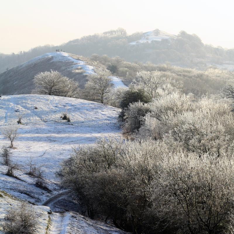 Ein Tag der verschneiten Winter auf den Malvern-Hügeln, schauend über der Kante mit einer Gruppe von Personen auf einen der Hügel stockbilder