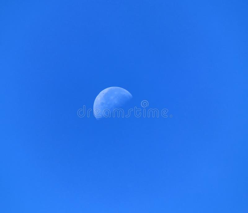 Ein Tagesmond in einem Hintergrund des blauen Himmels stockfotografie
