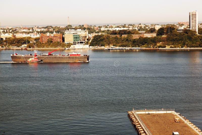 Ein Tanker, der durch Hudson- und Jersey-Skyline von NYC überschreitet stockbild