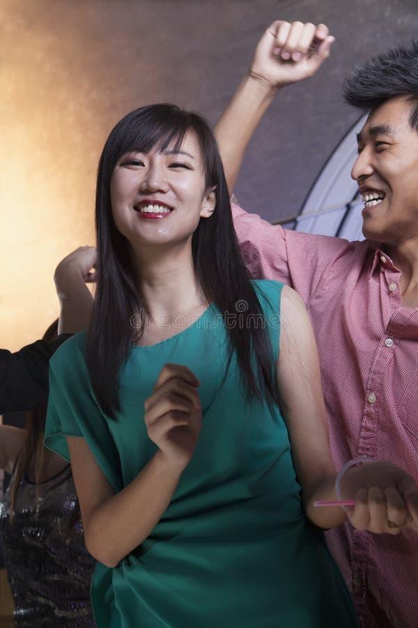 Ein Tanzen der jungen Frau mit Freunden in einem Nachtklub stockfotos