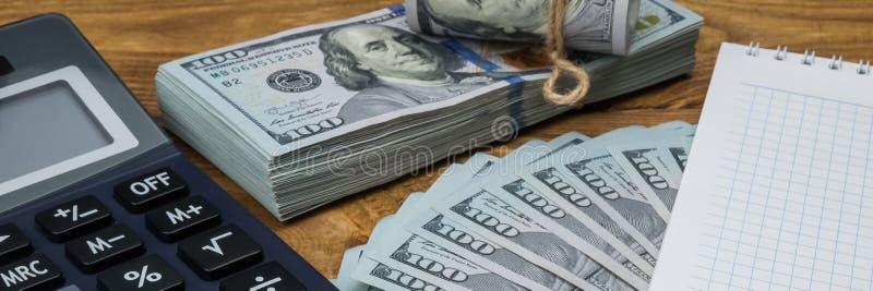 Ein Taschenrechner, Dollar in einem Bündel, eine Rolle und ein Fan, ein Notizbuch und eine Stiftlüge auf einer hölzernen struktur lizenzfreie stockfotos