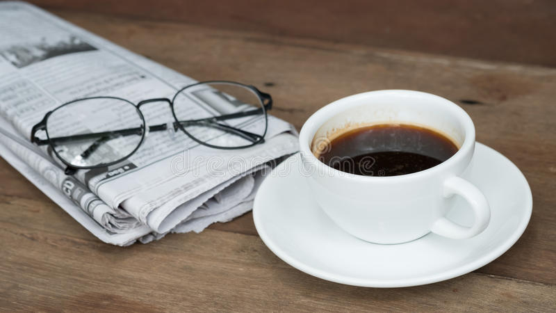 Ein Tasse Kaffee auf dem Tisch mit Zeitung lizenzfreies stockbild