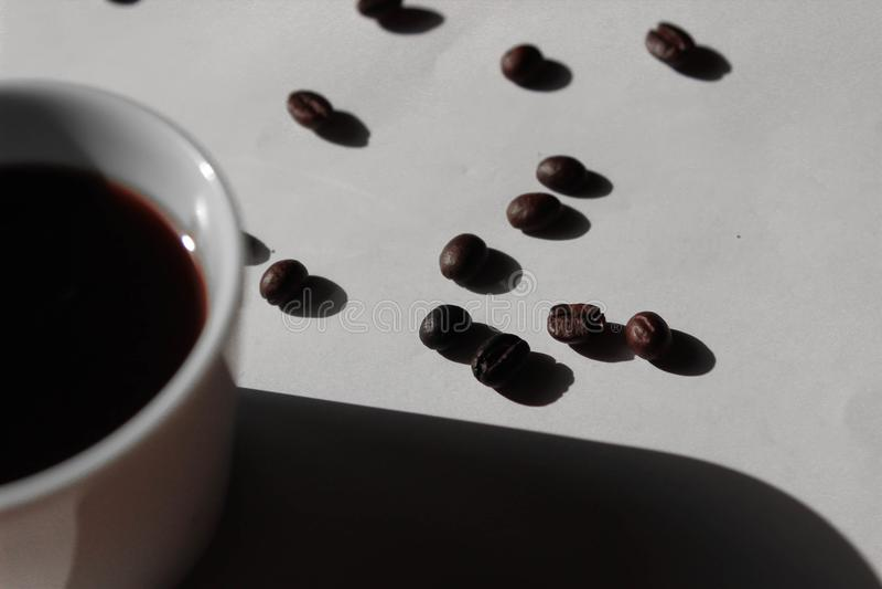 Ein Tasse Kaffee auf einem weißen Hintergrund mit Kaffeebohnen lizenzfreies stockbild