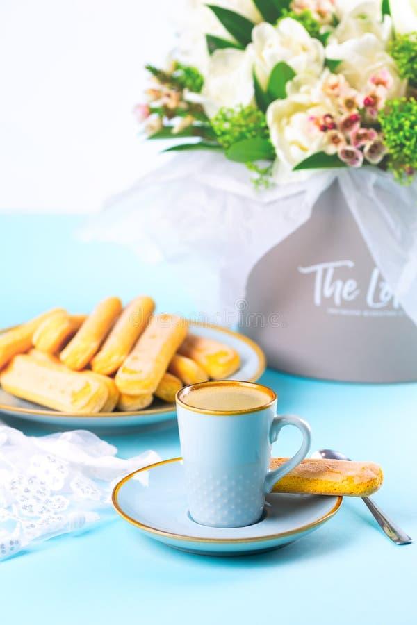 Ein Tasse Kaffee auf einer blauen Untertasse mit Savoyardi-Plätzchen lizenzfreie stockfotografie