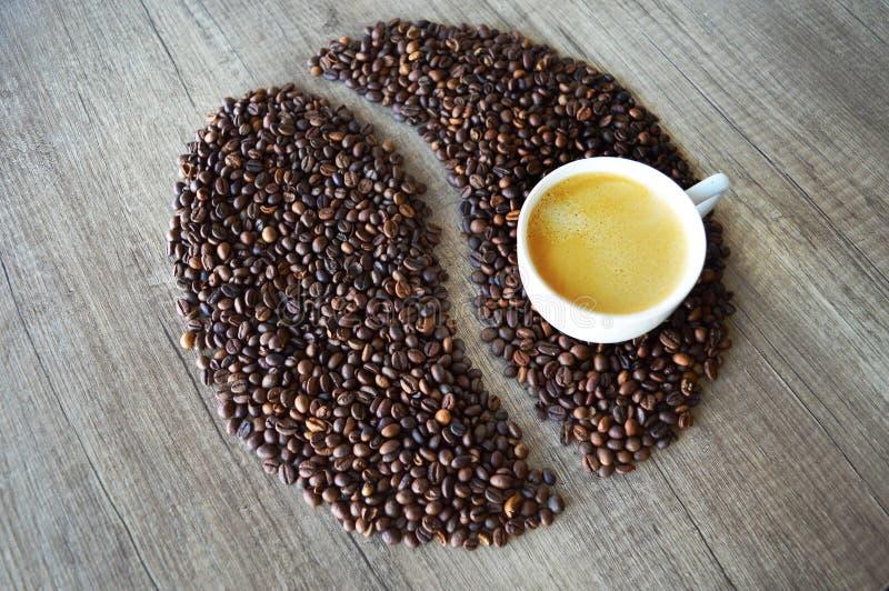 Ein Tasse Kaffee auf einer großen Kaffeebohne lizenzfreie stockfotos