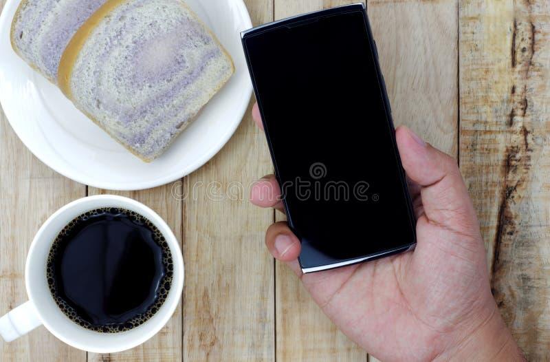 Ein Tasse Kaffee, Brot auf weißer Platte, Smartphone in der Hand auf flehen an stockbild