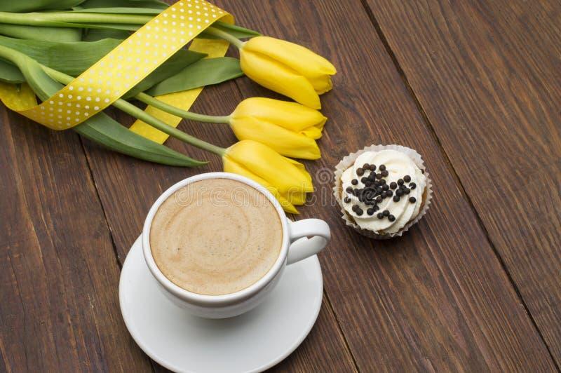 Ein Tasse Kaffee, ein capcake und ein Blumenstrauß von frischen gelben Tulpen auf einem hölzernen Hintergrund Romantisches Frühst lizenzfreies stockfoto