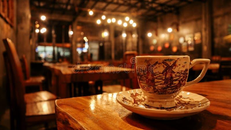 Ein Tasse Kaffee diente auf einem Holztisch mit einer ruhigen Ambientekaffeestube lizenzfreie stockfotografie