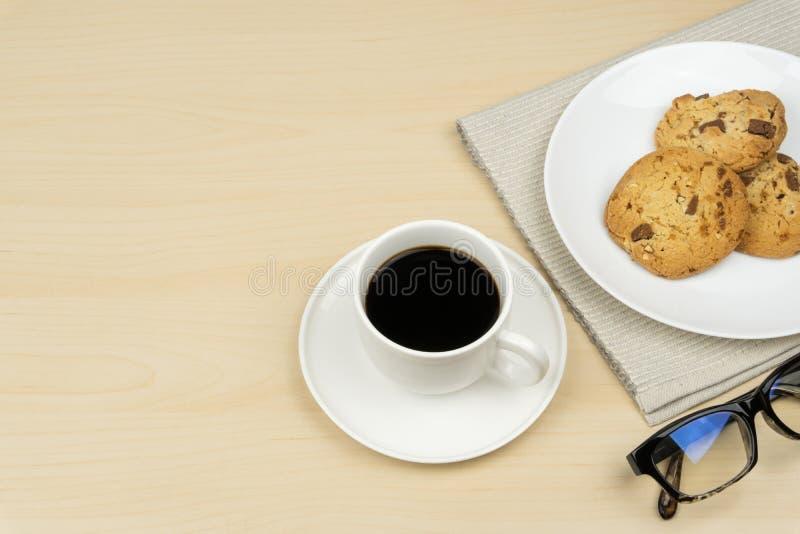 Ein Tasse Kaffee, drei Stücke Schokoladensplitterplätzchen in einem weißen runden Teller lizenzfreie stockfotografie