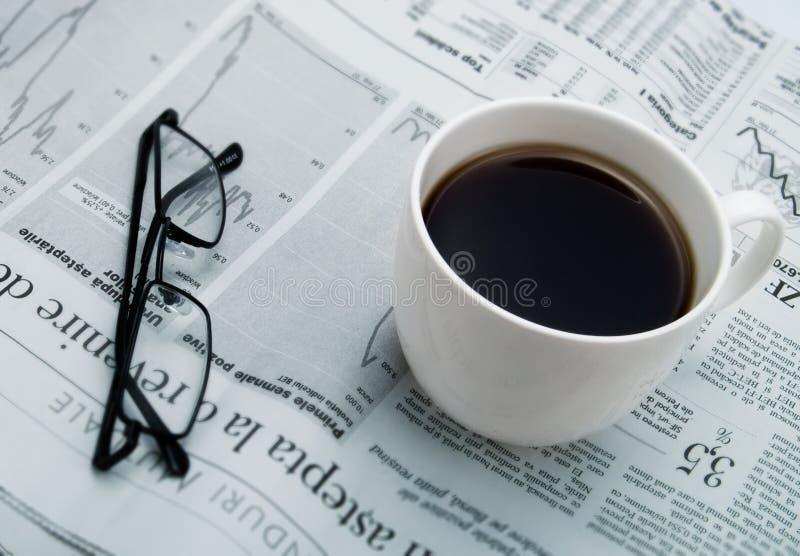 Ein Tasse Kaffee, Gläser und eine Zeitung lizenzfreie stockbilder
