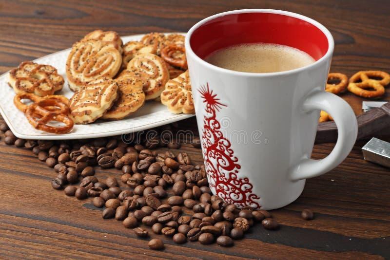Ein Tasse Kaffee, Körner des Kaffees und Plätzchen auf einem Holztisch stockfoto